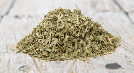 tarragon: Dried tarragon herb over wooden background