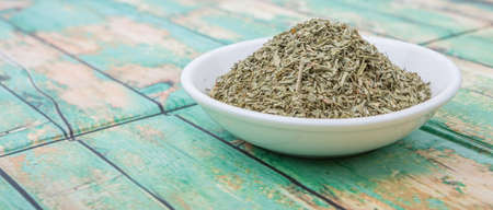 tarragon: Dried tarragon herb in white bowl over wooden background Stock Photo
