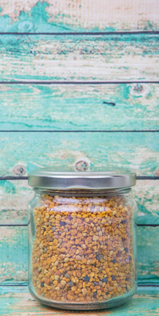 ambrosia: Bee pollen in a mason jar over wooden background