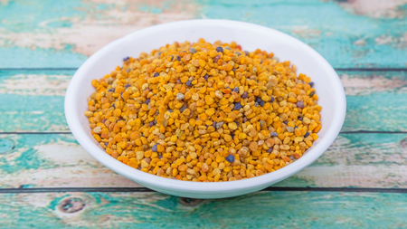 ambrosia: Bee pollen in white bowl over wooden background