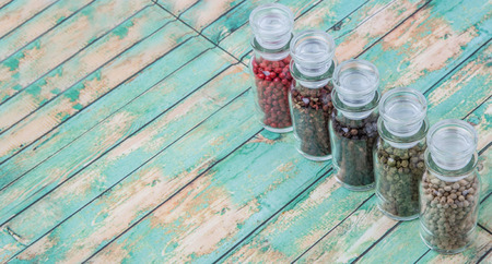 drupe: Szechuan peppercorns, green peppercorns, white peppercorns, black peppercorns and pink peppercorns in glass vial over wooden background