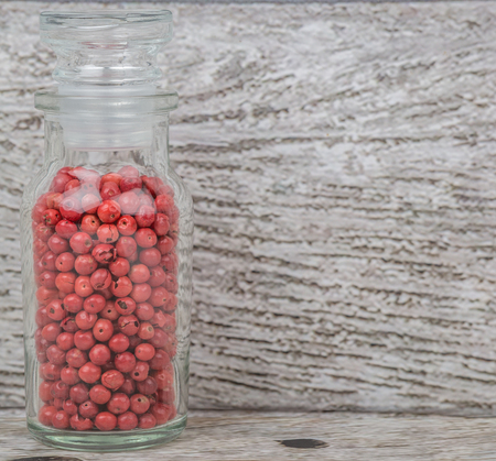 vial: Pink peppercorn in glass vial over wooden background