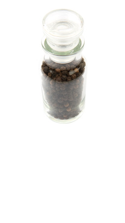 drupe: Black peppercorn in glass vial over white background