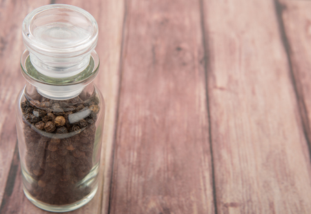 black peppercorn: Black peppercorn in glass vial over wooden background Stock Photo