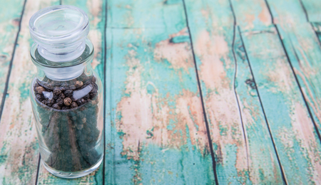 drupe: Black peppercorn in glass vial over wooden background Stock Photo