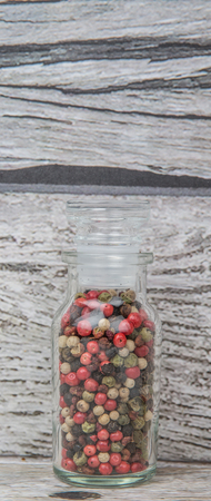 vial: Mix peppercorn variety in vial glass over wooden background Stock Photo