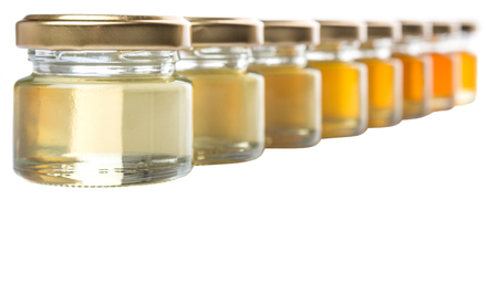 honey tone: Different grade and color of honey in mason jar over white background