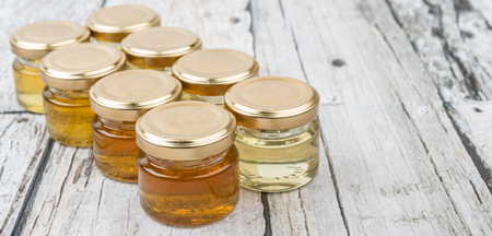 honey tone: Different grade and color of honey in mason jar over wooden background