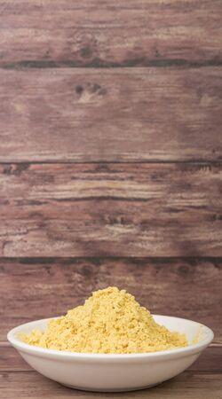 intense flavor: Ground mustard powder in white bowl over wooden background