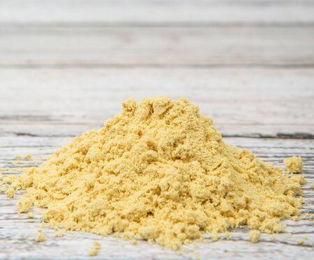 intense flavor: Ground mustard powder over wooden background