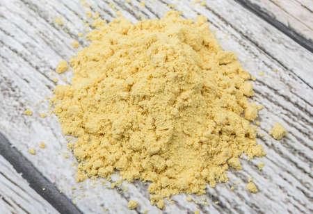 Ground mustard powder over wooden background