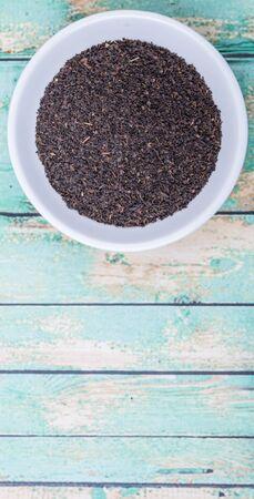 ceylon: Black Ceylon tea in white bowl over wooden background