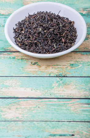 plant antioxidants: Loose dried darjeeling black tea leaves in white bowl over wooden background