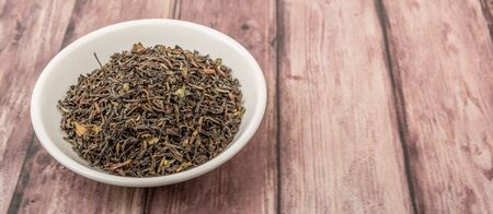 darjeeling: Loose dried darjeeling black tea leaves in white bowl over wooden background