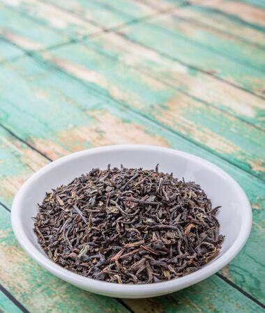darjeeling: Loose dried darjeeling black tea leaves in white bowl over wooden background