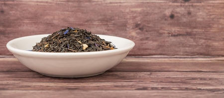 earl: Dried black Earl Grey tea leaves in white bowl over wooden background Stock Photo