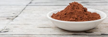 rich flavor: Cocoa powder in white bowl over wooden background