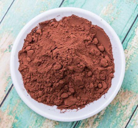dark brown: Cocoa powder in white bowl over wooden background