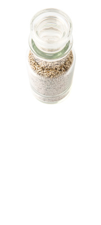 white chia: White chia seeds in glass vial over white background