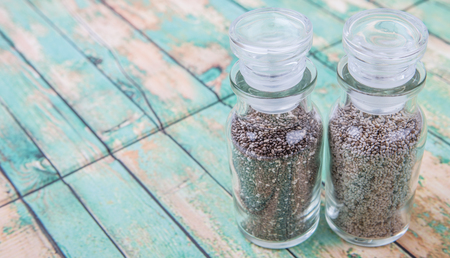 white chia: Black and white chia seeds in glass vial over wooden background