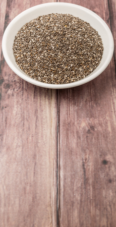 hispanica: Black chia seed in white bowl over wooden background
