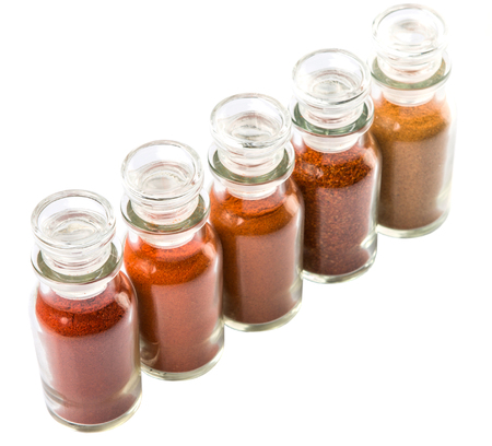chilly: Different type and colors of chilly powder, paprika powder, cayenne powder in glass vial over white background