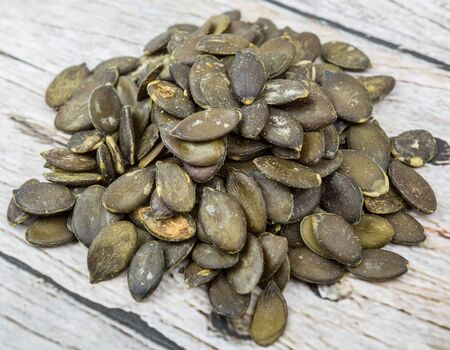 pumpkin seed: Roasted pumpkin seed over wooden background Stock Photo