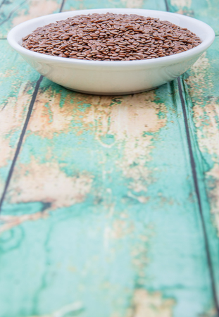 common flax: Flax seeds in white bowl over wooden background