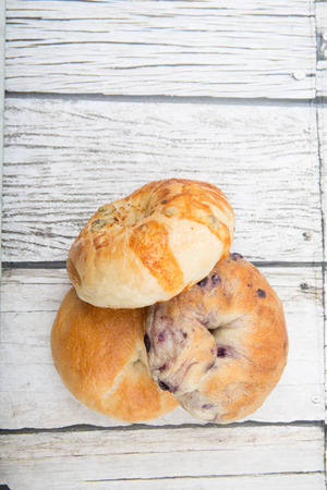 doughy: Homemade plain bagel, cheese bagel and blueberry bagel over wooden background