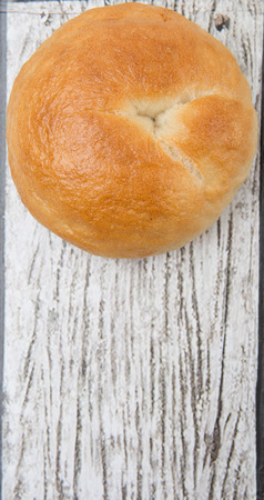 doughy: Plain homemade bagel over wooden background