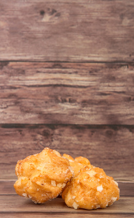 sprinkled: Choux pastry sprinkled with sugar over wooden background