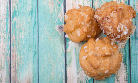 choux: Choux pastry sprinkled with sugar over wooden background