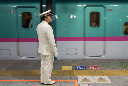 route master: TOKYO, JAPAN - MAY 30TH, 2016. Tokyo Railway Station officials working at the Tokyo Station terminal. Editorial