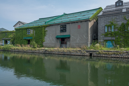 famous industries: OTARU CITY, JAPAN - AUGUST 1ST, 2016. Old stone warehouses lining up Otaru Canal in Otaru City, Japan. Otaru is popular tourist destination and a port city in the island of Hokkaido, Japan.