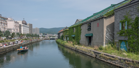 lining up: OTARU CITY, JAPAN - AUGUST 1ST, 2016. Old stone warehouses lining up Otaru Canal in Otaru City, Japan. Otaru is popular tourist destination and a port city in the island of Hokkaido, Japan.