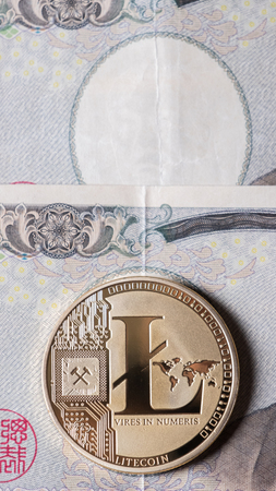 Litecoin cryptocurrency on Japanese Yen bank notes. Фото со стока