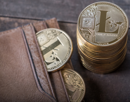 Litecoin with leather wallet on wooden table top