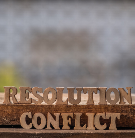 RESOLUTION and CONFLICT text on wooden background. Stock Photo