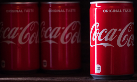 TOKYO, JAPAN - JUNE 17TH, 2018. Coca cola drinks on wooden table top with dark background