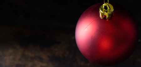 Red christmas balls on wooden board agaisnt dark background