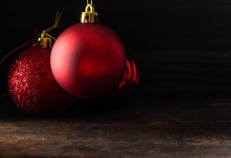 Red christmas balls on wooden board agaisnt dark background Standard-Bild - 105151126