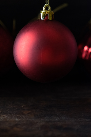 Red christmas balls on wooden board agaisnt dark background Standard-Bild - 105151141