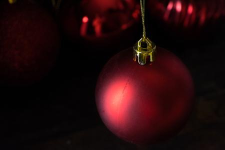 Red christmas balls on wooden board agaisnt dark background Standard-Bild - 105151360