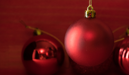 Christmas balls on over red wooden background