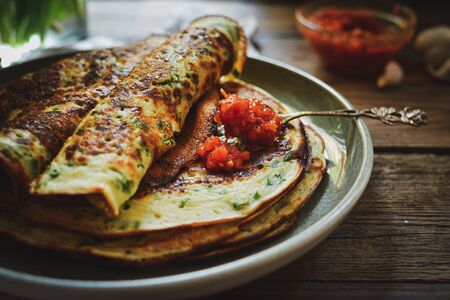 Thin pancakes with herbs. Salty Pancakes with green onions. Wood background. Vintage background. Delicious food for a bite to eat. Free space for text. Red sauce in a bowl.