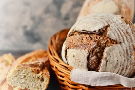 Bakery products in a wicker basket. Round homemade bread, long loaf with seeds, vegan bread without yeast.