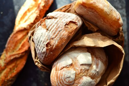 Bakery products. Crispy, beautiful bread on a dark background. Buckwheat, without yeast, wheat bread with flax and sunflower seeds. Top view, place for text. 版權商用圖片