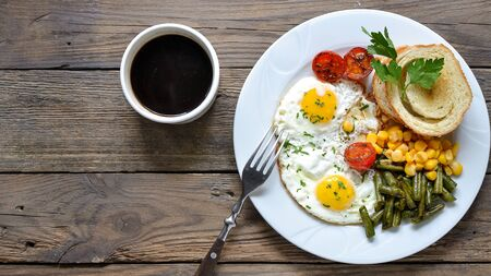 Fried eggs with tomatoes, green beans, corn and toast. English vegetarian breakfast. Top view. Coffee and fried eggs on a wooden tray. Wood background Standard-Bild