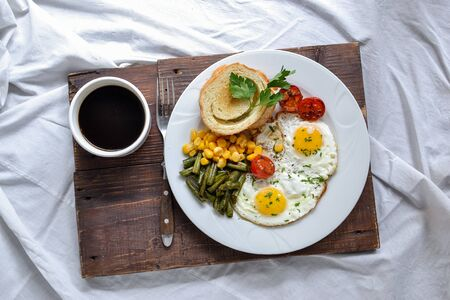 Breakfast in bed. Fried eggs with tomatoes, green beans, corn and toast. English vegetarian breakfast. Top view.