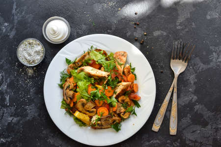 Grilled vegetables and chicken salad. Chicken breast, salad, mushrooms, tomatoes, orange. Top view. Free space for text. Dark background